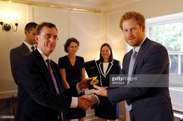 Prince Harry (R) presents U.S. Staff Sergeant Elizabeth Marks' gold medal to Consultant Intensivist Dr Alain Vuylsteke (L) and the other members of the medical team from Britain's Papworth Hospital at Kensington Palace on June 1, 2016 in London, England. At the 2016 Invictus Games in Orlando, U.S. Staff Sergeant Elizabeth Marks asked Prince Harry to present her 100m swimming freestyle medal to the team at Papworth Hospital, who she credits for saving her life.
