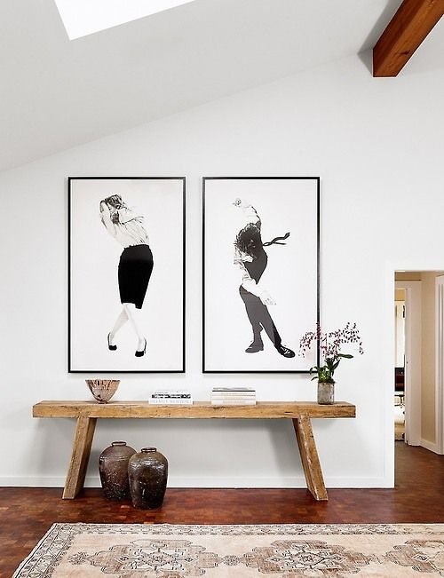 Oversized prints above a wooden bench