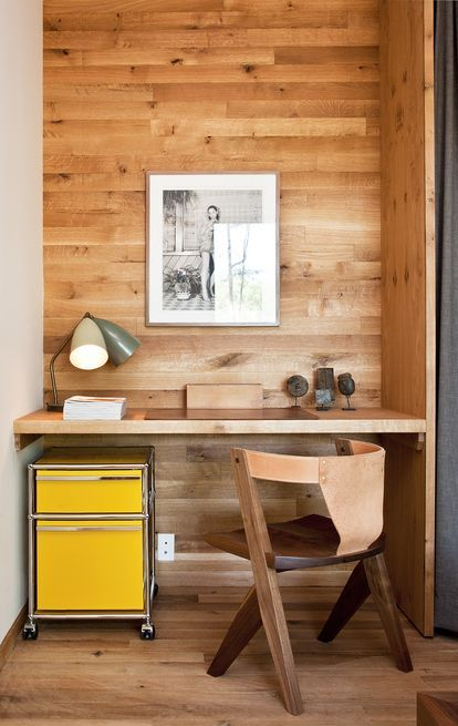 At Hudson Woods, a community of modern cottages in Hudson Valley, New York, a tidy desk gets a punch of color from a yellow Pedestal filing cabinet byUSM. The table is paired with aleather-back chair designed byMichael Robbins.  Photo by Deborah DeGraffenreid.