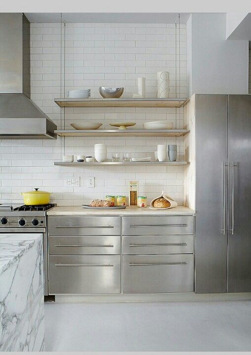 Sleek, modern white kitchen, suspended shelving. The stainless cabinetry gives a professional look! The marble island gives a soft touch!