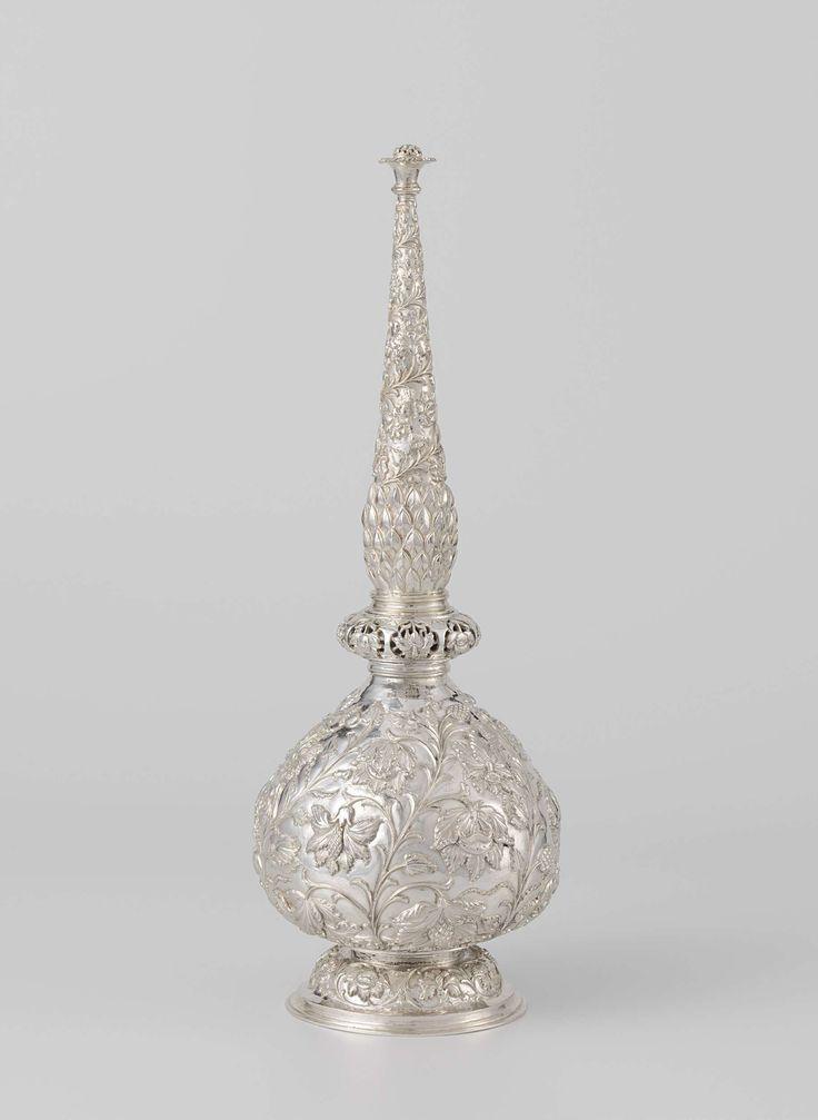 | Rozenwaterflacon van zilver, gedreven met bloem- en bladranken, 1700 - 1799 | Rozenwaterflacon van zilver op geprofileerde voet met peervormig lichaam en afschroefbare langgerekte hals eindigend in een bloemvormige piek. Tussen de meeldraden van de bloemen zitten gaten. De gehele flacon is versierd met bloem- en bladranken. Boven de nodusvormige verbreding aan de onderzijde van de hals zien we een decoratie van puntige schubsgewijze geplaatste bladeren (ananas?). India of Sri Lanka, 18de…