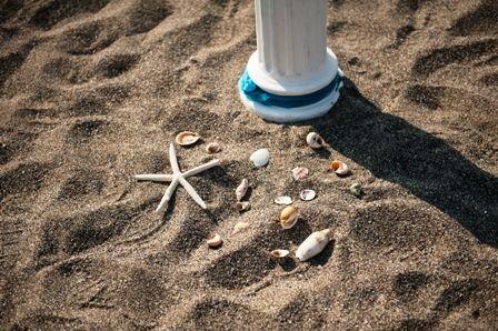 Starfish & seashell decoration items beside white wedding pillar for your perfect destination wedding in Crete. Moments www.weddingincrete.com