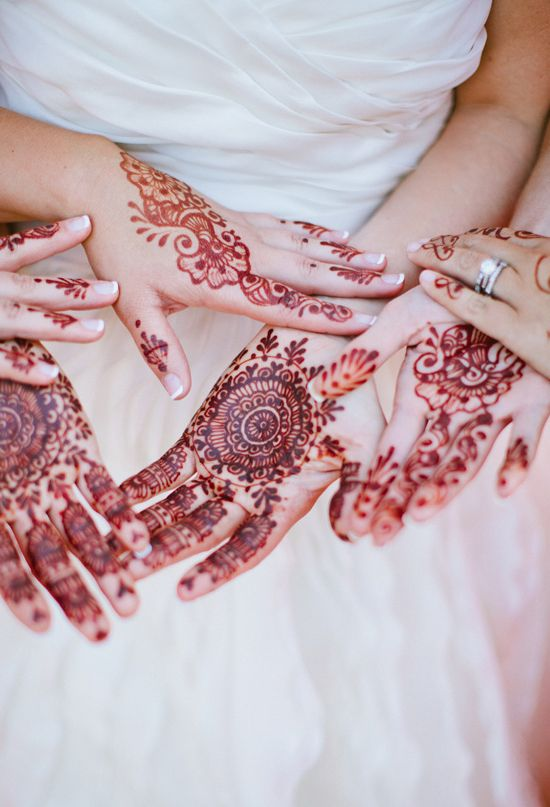 mixing east and west - this bride and her bridesmaids got traditional henna designs painted on their hands in honor of the indian groom