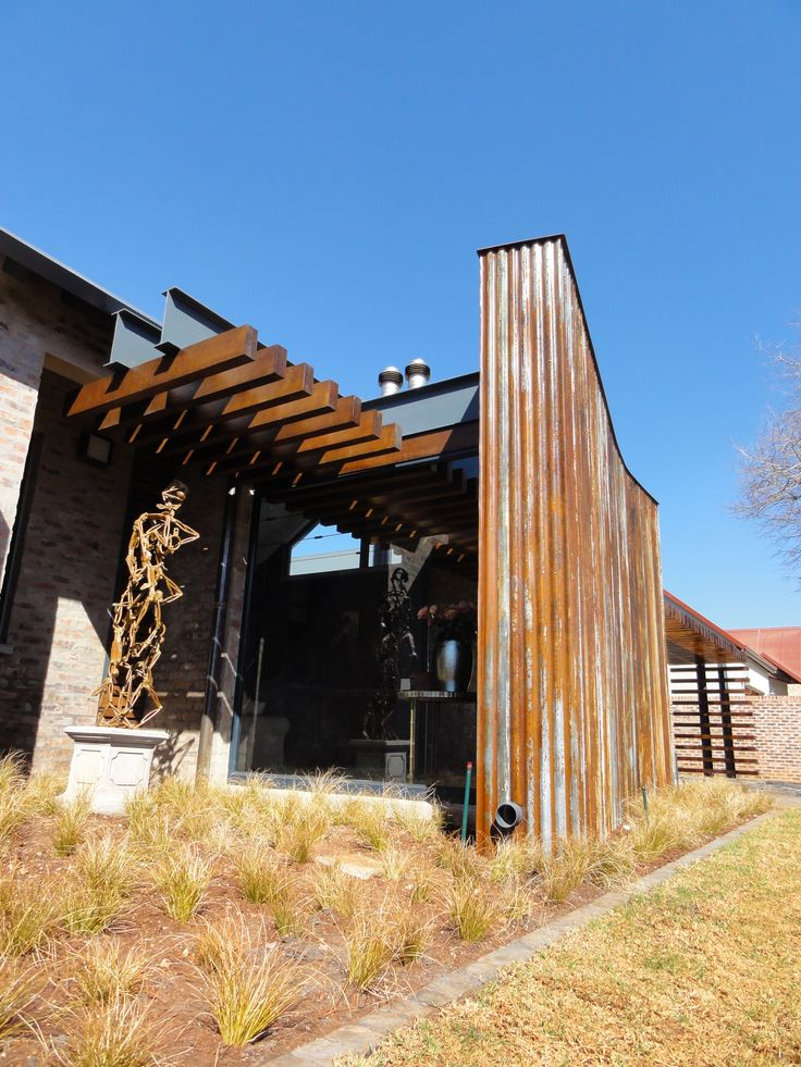 House Uys in Pretoria, South Africa. This is a single storey home built in a farming estate and located with views over the neighboring golf course, enjoying the best of both worlds. A steel I-beam and wood structure, reminiscent of an elongated spine, frames the western facade from the street, while leading the eye to the front door. Completed 2010 by Mathews and Associates Architects. Photo courtesy of Pieter Mathews. Sculpture by Sybrand Wiechers.