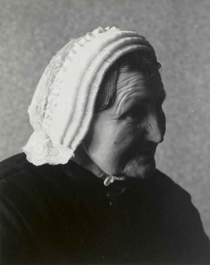 Vrouw uit Seerijp in Terschellinger streekdracht. De vrouw is gekleed in de zondagse dracht of opknapdracht. Ze draagt de 'driestrokenmuts'. Deze muts bestaat uit een bol, voorstrook en achterstrook. De voorstrook bestaat uit drie gepijpte tule stroken met daarachter een rand, gevormd door twee dooreengevlochten witte bandjes, de zgn. 'dopkes'. De achterstrook, het zgn. 'nekje', is gemaakt van Engels borduurwerk. 1950 #Terschelling
