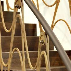 www.trabczynski.com  ST890 Łukowe schody dywanowe wykonane z dębu wędzonego. Balustrada z cortenu i mosiądzu, pochwyt wykończany skórą. Projekt – TRĄBCZYŃSKI
