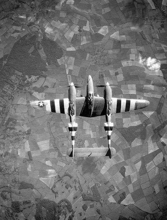Top view of a P-38 Lightning aircraft in flight over the English countryside June 1944.
