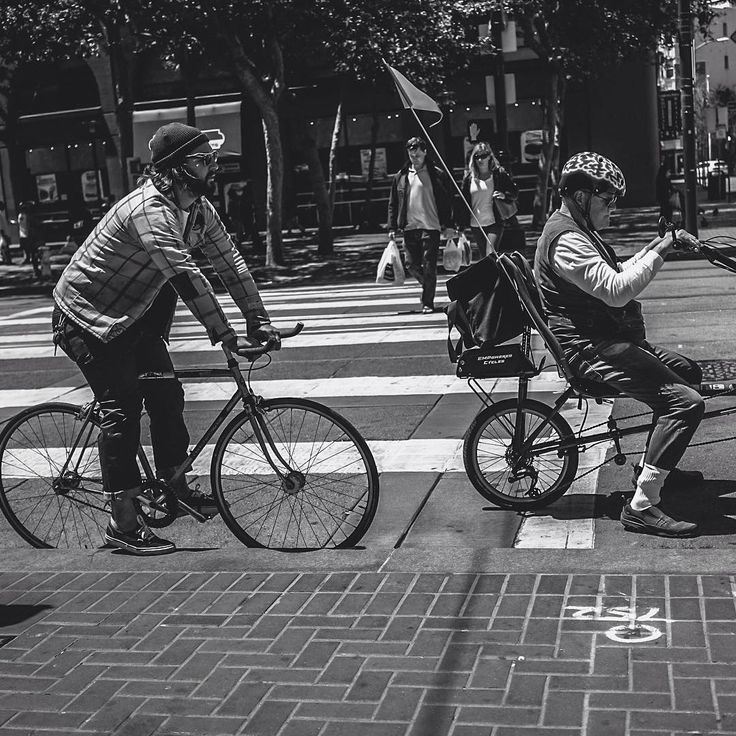 Two bicyclists patiently wait at a crosswalk