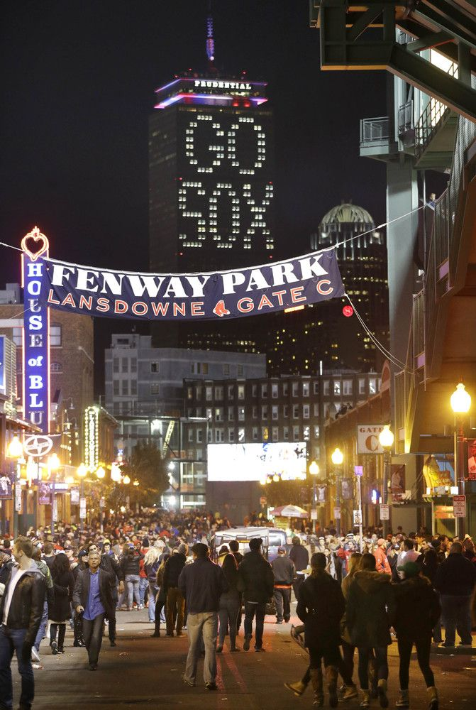 The words 'GO SOX' are illuminated on a side of the Prudential Tower, top, as people walk along outside of Fenway Park during Game 6 of the World Series.