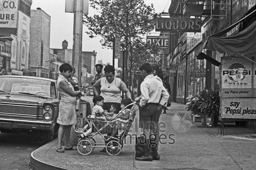 Familie in Harlem, 1967 Hermann Schröer/Timeline Images #1960er #1960ies #familie #family #historisch #historical #retro #vintage #NewYork #harlem #kids #buggy #Straßenecke #Mutter #Mütter #Kind #Kinder
