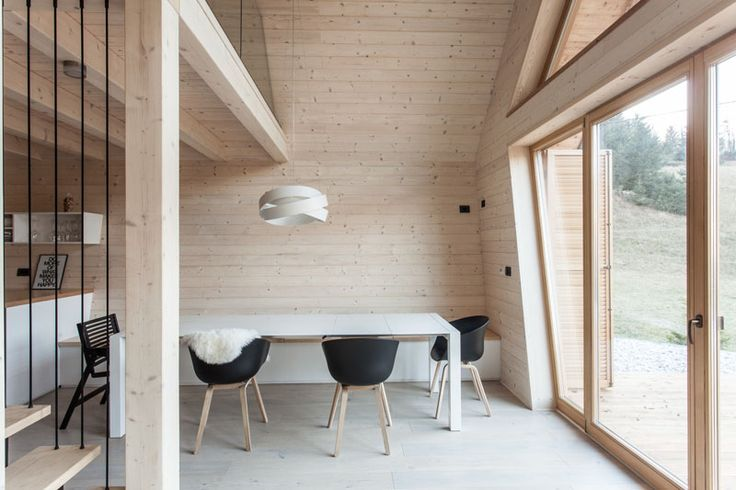 In this modern light wood and white dining room, a bench is built-in along the wall to save room.
