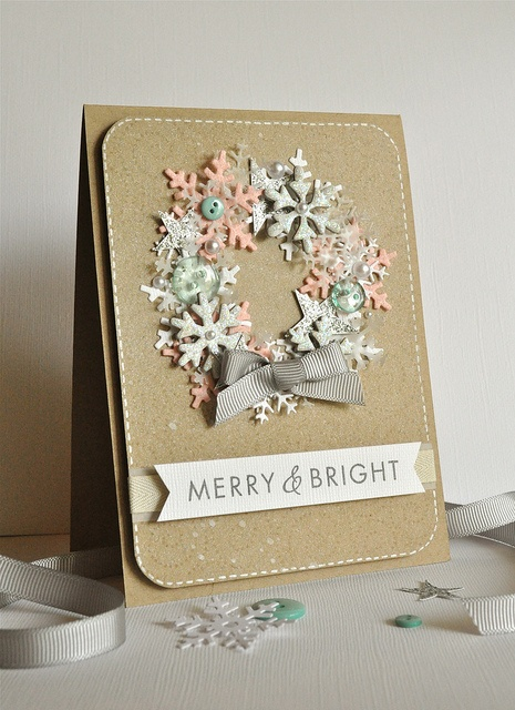 wreath out of pink and green pastel snowflakes with stars behind the snowflakes.  Ribbon at bottom of wreath.  Banner with message on bottom of the card.
