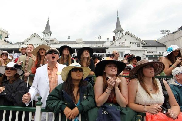 Fans watch a race on a video screen during the 137th Kentucky Derby at Churchill Downs.