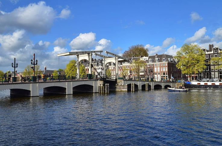 The Magere Brug (aka Skinny Bridge) is a bridge over the river Amstel in Amsterdam  #amsterdam #netherlands #travel #amsterdamworld #afternoon #magerebrug #skinnybridge #bridge #amstel #river #water #riverbank #bluesky #clouds #street #streetphotography #nikon #nikonphotography