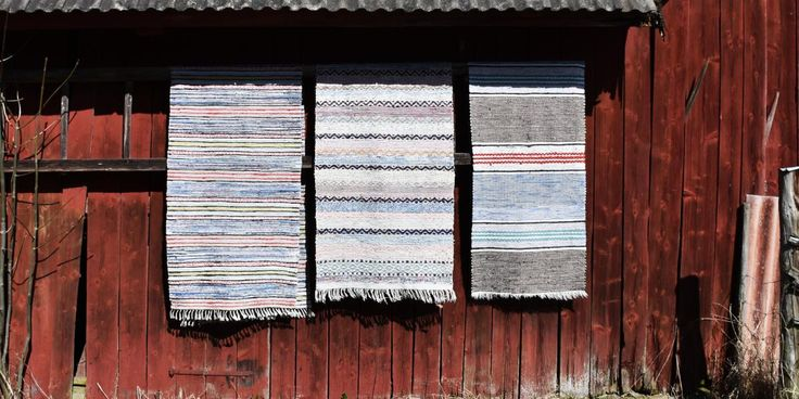 """Swedish """"falu rödfärg"""" wall with beautiful vintage rag rugs.   We sell beautiful, vintage and antique Swedish rag rugs. These rugs are not only beautiful, they are pieces of history brought to your awareness. Each rug tells you its lively and soulful story. You can only imagine its proud creator and former owners. Now it's your turn to fall in love. Welcome to a world of Swedish rag rugs.."""