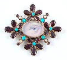 "Late C18th Georgian eye miniature painted in watercolor on ivory wreathed with garnet and turquoise pansies, pearls, and hair on the reverse.    From Kyle Karnes on the symbolism of the stones and flowers. ""From the French word pensée, the pansy is a pun meaning ""think of me."" The turquoise, owing to its color, was symbolic of the flower, ""forget-me-not,"" and the pearls symbolized tears."""