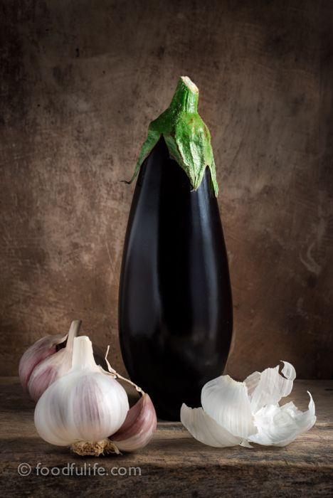 Aubergine with garlic on wood