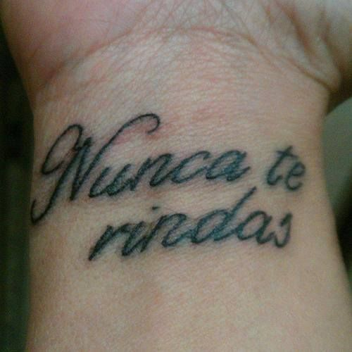 Little wrist tattoo saying nunca te rindas spanish for Tattoo tip percentage