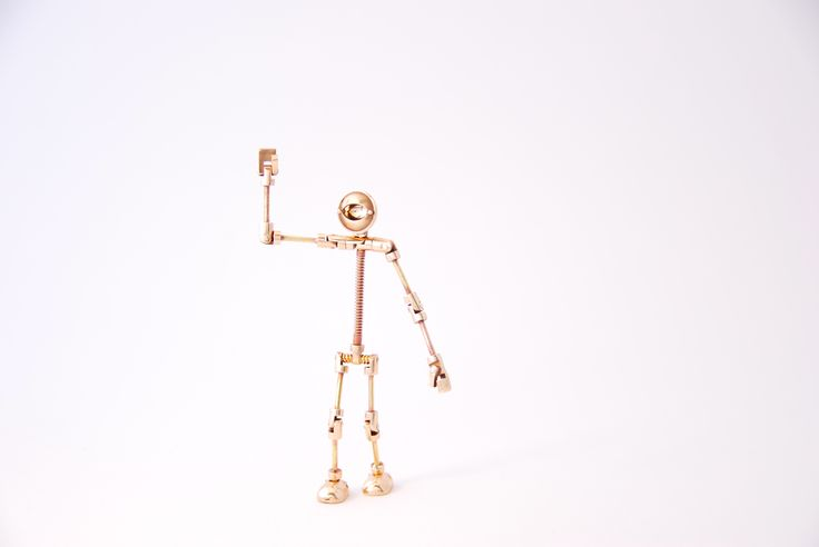 Quinbot by Juhani Ananin. Steampunk miniature made from silver, brass, steel spring and bronze with a 18 carat yellow gold eyeplate. 2 x 9 x 0,5 cm.  Oh! Hello!  Photo: Hanna Silander