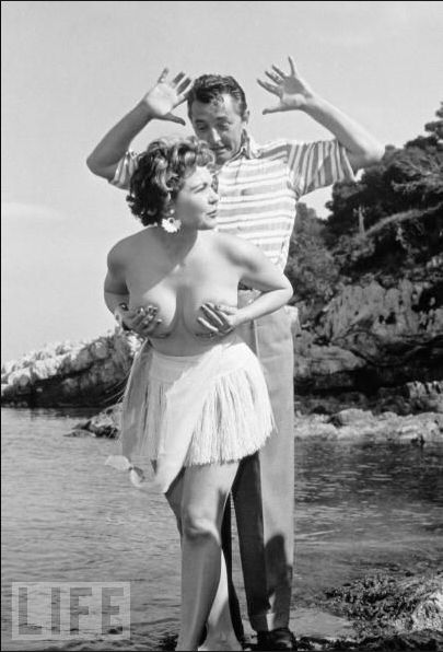 """Miss Festival"" Simone Silva poses topless with Robert Mitchum during the Cannes Film Festival in April 1954."