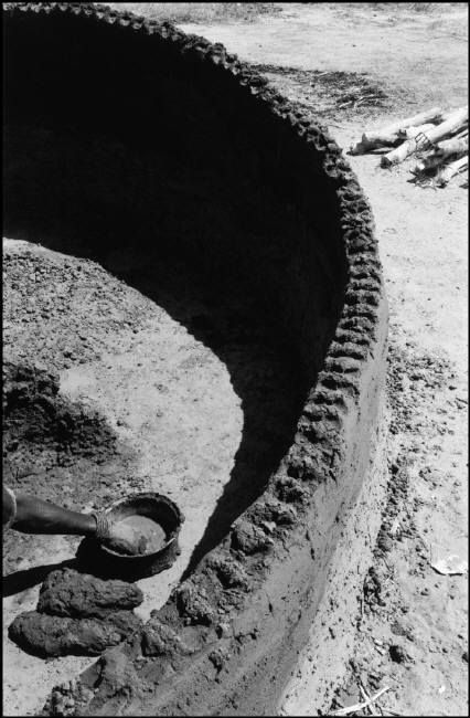 """John Vink  Village of Bileyl (South of Darfour). 10/11/88. South Sudan moving families. Building of a clay hut (""""tukul"""")."""