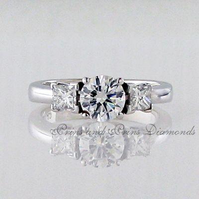 Centre diamond is a 1.012ct G/VS2 round brilliant cut diamond with 2 = 0.47ct princess cut diamonds set in 18k white gold