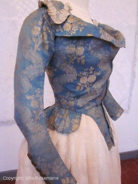 "this  bodice called ""Pierrot"", short jacket fitted to small Basque illustrates the  transition of the fashion at that time. The fabric which is blue ""Nattier"" taffeta silk brocaded gold with ""décors à la rivière "", probably seems to be earlier. This ""Pierrot"" was often worn with a, embroidered cotton gauze skirt. Fully lined with white linen. Pleated ribbon ivory silk faille on the neck and six steel buttons on each wrist"