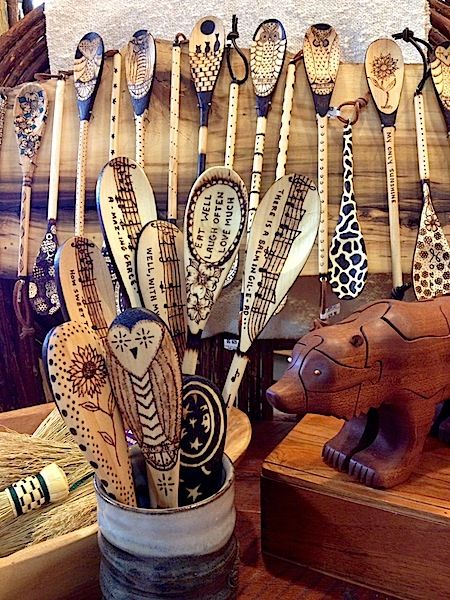 Wood burned spoons. A large variety of spoons can be seen in this photo, most of the idea's are quite famiar to us all. But if you take a closer look there are a couple of diferences here & there. One is using the music staves along the length of the spoon faces, I hadn't seen that before & back right are 2 rather dramatic patterned ones, also using those strong dark collars does draw the eye& help build your statement ;)