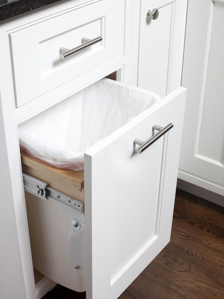 A Pull Out Trash Bin Integrated Into The Base Of A Cabinet Keeps Bins For