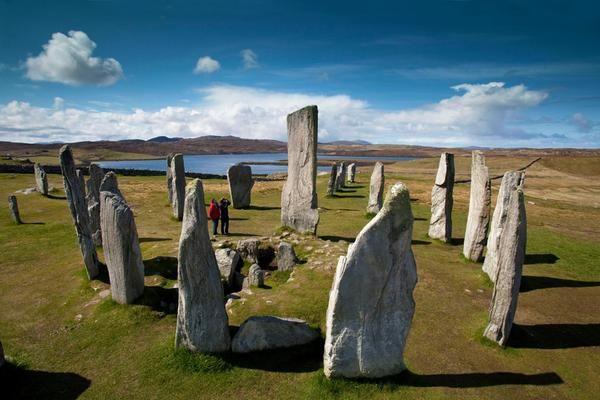 Un couple de visiteurs admire les menhirs de Calanais sur l'île de Lewis lors d'une belle journée