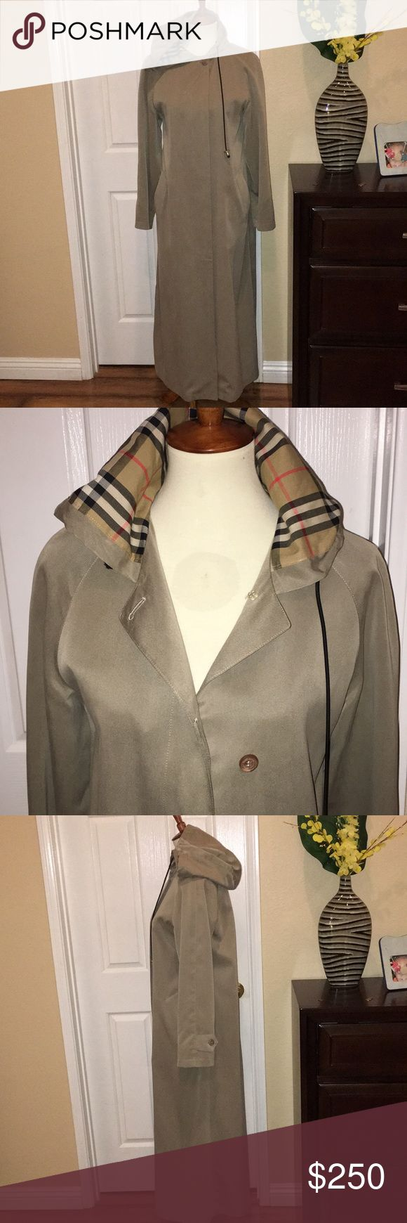 BURBERRY LONDON WOMENS RAINCOAT Color is a grayish beige, falls below the calf with a long slit. Partially lined through the upper back and sleeves with attached hoodie. Dry clean with special care. DoNotWash. Polyester, rayon, viscose. Lining polyester and cotton. Very stylish and unusual. This an authentic item so spare me the cross-examination about receipts and codes and witnesses. Burberry Jackets & Coats #RaincoatsForWomenLondon