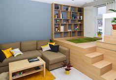 """Obývací kút nadväzuje na """"medziposchodie"""", kde sa nachádza knižnica. Vedľa nej možno vytvoriť čitáreň alebo umiestniť prístelku pre hostí. Celá konštrukcia je vytvorená z pórobetónových tvaroviek a obložená laminátom v dekore dub ferrara. Priestor pod posteľou slúži ako šatník.  - image thumbnail"""