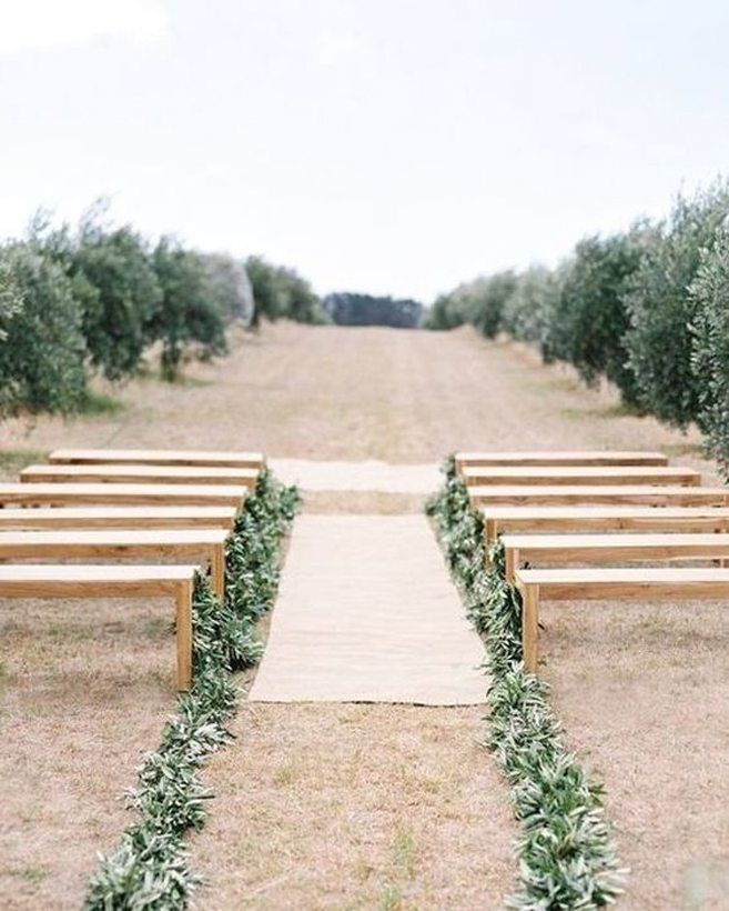 If you're going for a fresh and minimal look, keep your ceremony space simple with just a few benches and a garland of greenery running all the way down both sides of the aisle.     Image via  Once Wed/Instagram.