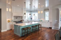 Amazing kitchen with white perimeter cabinets painted Benjamin Moore White Heron paired with white countertops framing paneled range hood accented with swing-arm pot filler over integrated Wolf Range across from blue gray kitchen island painted Benjamin Moore Wedgewood Gray paired with farmhouse sink and gooseneck faucet illuminated by Hicks Pendants in Polished Nickel. Kitchen with corner sink situated under window and next to small stainless steel mini-fridge.