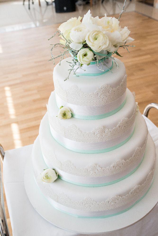 Čtyřpatrový svatební dort obalený bílým fondánem, dozdobený saténovými stuhami, jedlou krajkou a živými květinami.