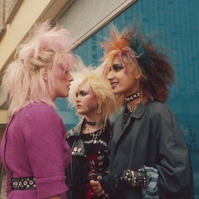 [Color photo of punk/post-punk ladies hangin' out in smiling conversation]