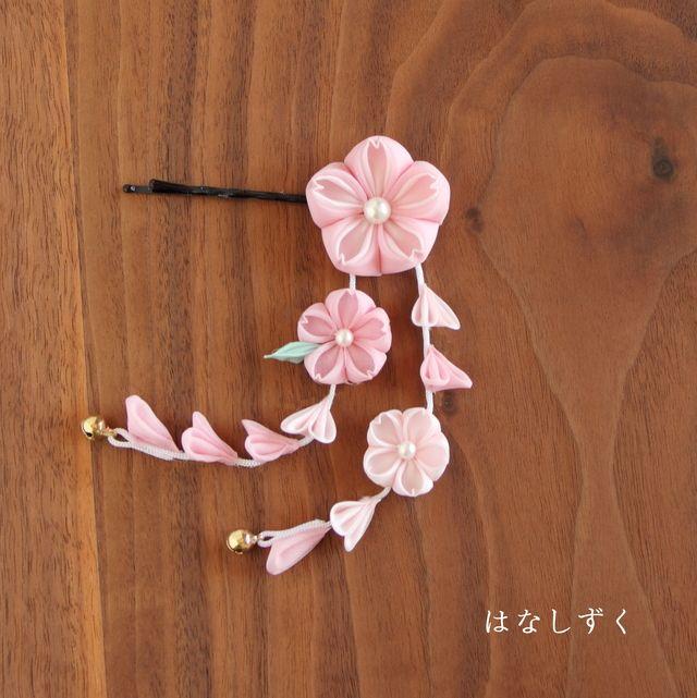 ご覧いただきありがとうございます。正方形の布を折りたたんで作るつまみ細工のヘアピンです。下がりにも花をつけたとても可愛らしい仕上がりになっております。色は大きい桜が桃色と桜色の二重花、下がりの花は桜色と桃色、葉っぱは薄緑です。下がりには6ミリ宝来鈴がつい...