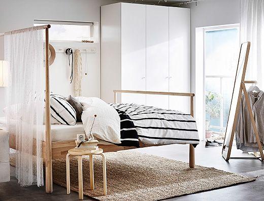 Quarto com uma cama em bétula maciça com o fundo mais alto e um tecido transparente que também serve como divisória. Apresentado com um roupeiro branco e um espelho de pé com arrumação atrás.