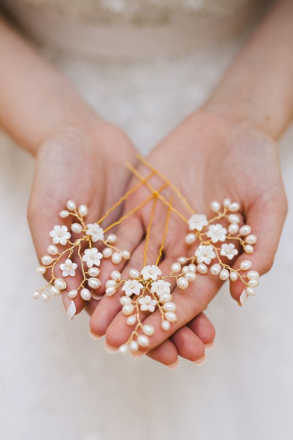 Add some elegance to your tresses the Claudette wedding hair pins. Each delicate pin features a sweet spray of pearls and flowers. Scatter the hair pins throughout your hairstyle for a romantic look, or tuck them in as a group for a bolder look that echos fine French lace. DETAILS • Set of three hair pins. • Adorned portion measures 5 cm. (2) long and 4 cm. (1.75) across widest point. • Hand wired genuine freshwater rice pearls.. • Carved mother of pearl flowers. • Available in gold as sh...