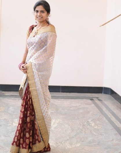 Saree:half white net and maroon brocade saree with a golden patch work and a velvet border with a brocade blouse.