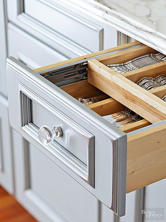 Two-tier drawers maximize every square inch of storage space. Trim features and glass knobs on surrounding cabinetry provide elegance on top of efficiency./