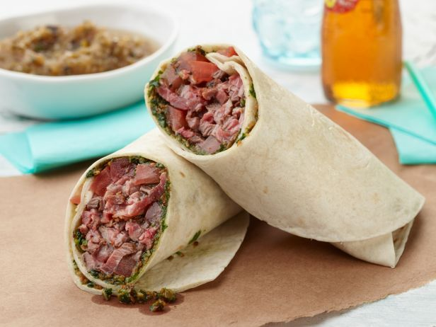 Carne Asada Burrito : Jeff makes a mojo marinade for steak before grilling it until charred and crusty. Pile the steak onto tortillas smeared with a layer of cilantro pesto, then sprinkle with tomatoes. Wrap it up tight and eat whole, or slice in half on the bias — just don't forget to dunk it in plenty of homemade salsa.