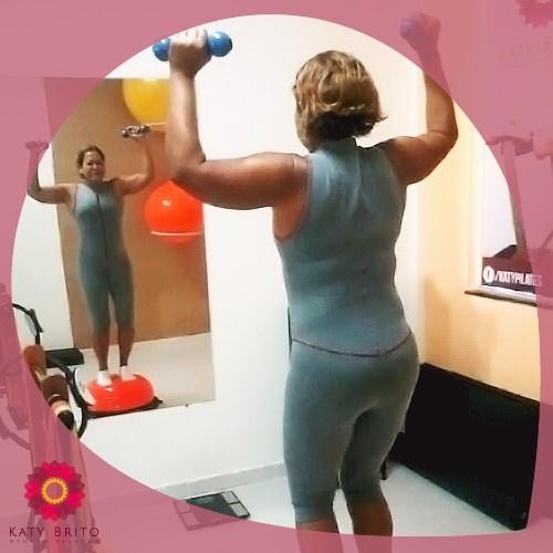 """A aluna Lilian Nogueira, 57 anos, realizando um exercício de desenvolvimento de ombro em uma base instável """"meia bola bozu"""".  Além do fortalecimento do ombro, a musculatura profunda do abdome também é trabalhada de forma intensa. O controle da respiração e a concentração são essenciais para a execução do movimento em equilíbrio."""