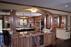 Die Inspiration verfügt über eine Idee für eine elegante Holz-Themen-Küche mit einem Bogen über die Küchenbar mit im Set Holz Schränke, Pendelleuchten und Kücheninsel mit schwarzen Stuhl. Es hat auch Edelstahlgeräte, Shaker-Schränke, mittlerer Ton Holz Schränke und Beige Backsplash. Die Insel und die Bar bieten auch Granit-Arbeitsplatten. Quelle: barteltremodel.com