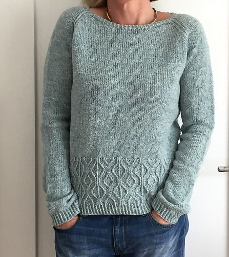Worked seamlessly from the top down, this pullover features a raglan yoke, a lovely textured pattern band right before the bottom ribbing, and in-the-round construction for both body and the sleeves. The yoke begins with short-rows worked back and forth, then joined to work in the round with raglan increases. Twisted stitches add texture to the raglan lines. As this pullover is worked from the top down it is advisable to try it on from time to time to check the length and overall fit. The…