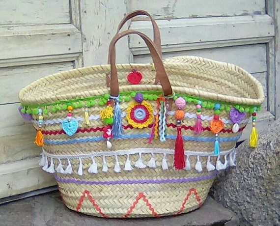 These trendy boho ibiza style bags are the ultimate must have for this summer . This unique bag was handwoven with natural palm leafs in Morocco and then decorated with a lot of handmade colourful details.  Perfect for the beach, shopping, ecc.  The measure is aprox 53 cm across the top and 32 cm tall. It comes with short flat leather handles .