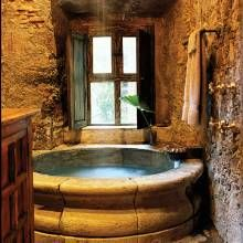 The master bath's cantera tub includes a rain-shower fixture. Once an open space, the room was constructed of stone walls to match the home's original walls.