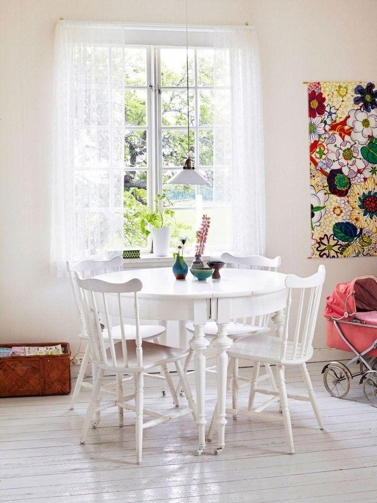 I vardagsrummet står en matgrupp av loppisstolar och ett vitmålat bord som tillhörde huset. Tyg på väggen, Svenskt Tenn. Dockvagn köpt på blocket till dottern Ida. Möbleringen i rummen har fått växa fram genom åren. Nu genomsyras inredningen av färgstarka och mönstrade textilier i retroanda, mot en vit bas.