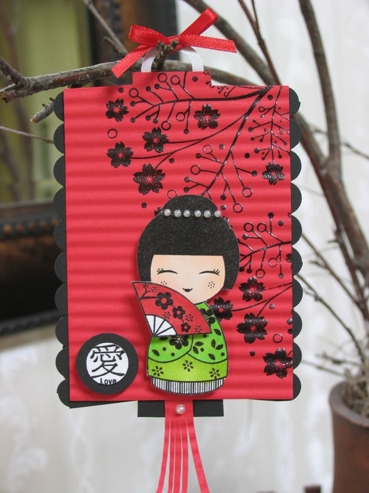 handmade card/ornament ... shaped like a lantern of red paper crimped like pleats in lantern ... adorable kokeche (sp?) doll with fan  on top ...