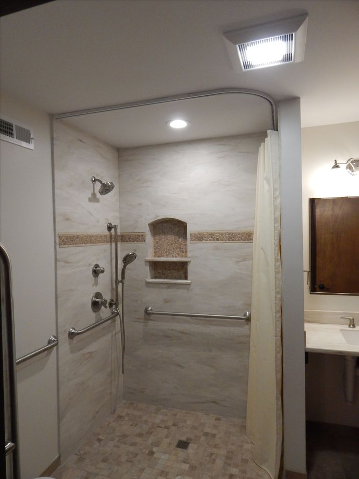 This is our custom build zero barrier shower with Corian wall surround in the color Witch Hazel and a stone accent. Note the shower curtain is suspended from the ceiling which allowed it to tuck back behind the end wall on demand.